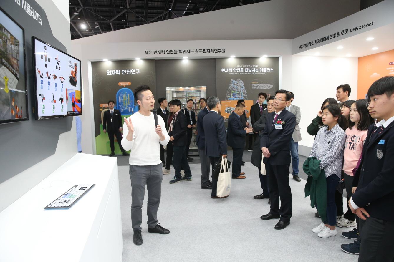 사진2. 전시회 관람객들이 원자력발전소 로봇 시뮬레이터 사용법에 대한 설명을 듣고 있다.